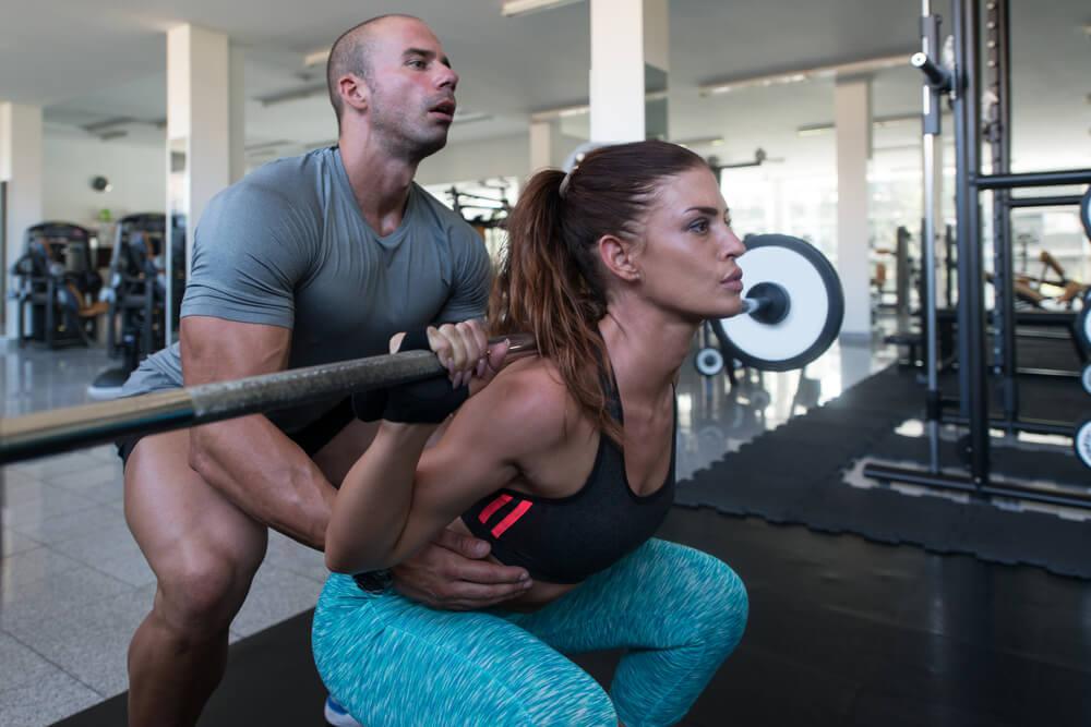 vrouw-back-squat--met-spotter