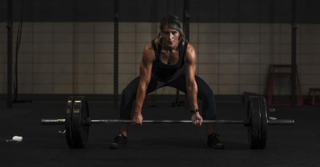 Vrouw in de gym met een barbell