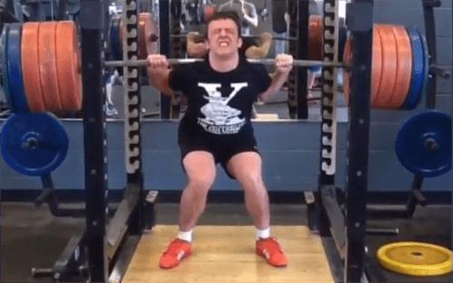 Man squat met zwaar gewicht en ingevallen knieën
